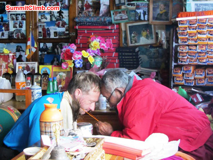 Mark van 't Hof receives his blessing from Lama Geshe in Pangboche. Note the prayer books and summit photos in the background. Photo by Maggie Noodle.