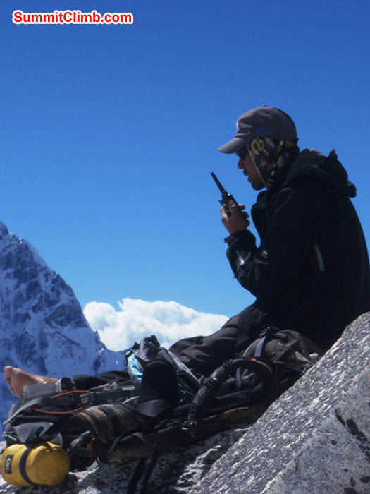 Tenji Sherpa, with bare foot, makes a radio call from camp 1. Photo James Barritt.