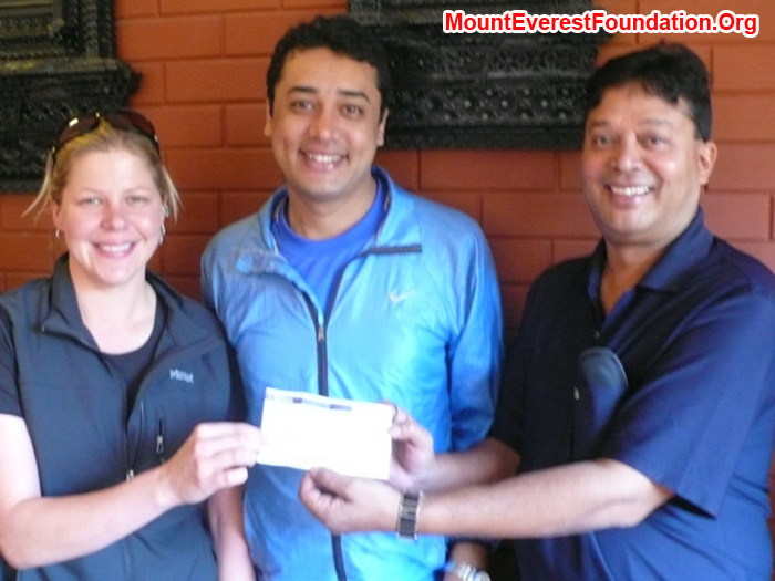 Holly budge presenting a cheque to Mount Everest Foundation directors Murari Sharma and Deha Shrestha.