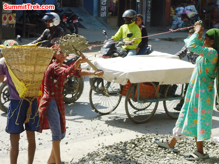 Kathmandu - motorcyclists drive past, while a peddlers rolls a fruit cart covered with a white sheet. 2 women load basket with gravel, one with shovel and other aiding with rope tied to shovel. Photo Carla Strong