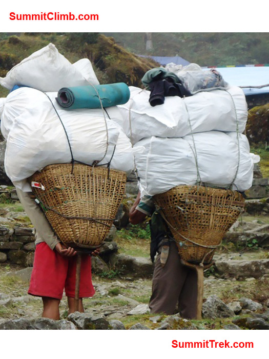 Two porters with big loads in Chutanga. photo by Carla Strong