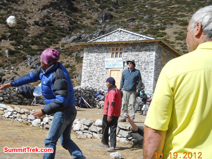 Joe, Stewart, and Sange watch Nawang Sherpa tossing a rock in the village lawn bowling competition in Tagnag at 4000 metres / 13,120 feet. Photo by Jennifer Klich.