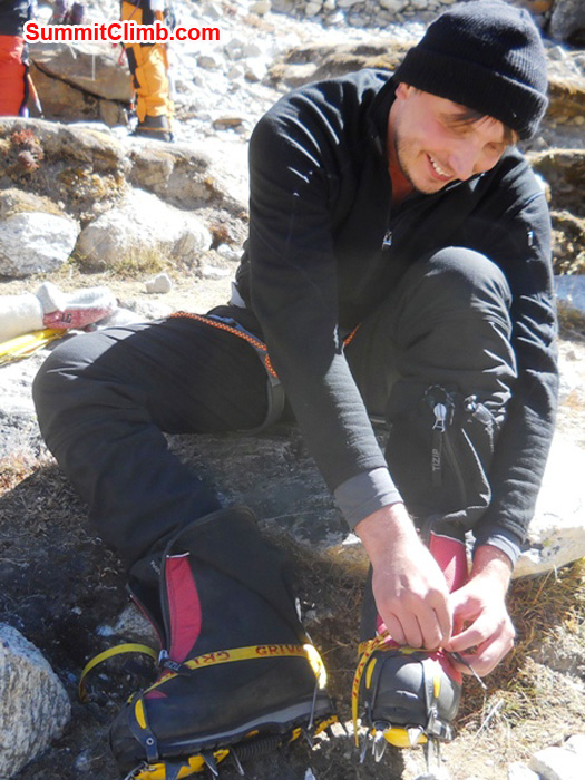 Frank puts on his crampons in Kare Village during a practice session. Photo by Jennifer Klich