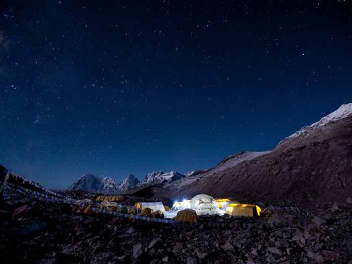 A climber from Seattle, disturbed by the amount of waste he saw being generated at Everest base camp (seen here at night), helped start the Mount Everest Biogas Project to turn that waste into energy. Below, porters carry waste away from base camp. Photograph by Alex Treadway, National Geographic
