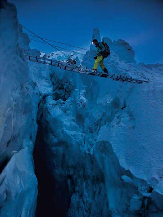 Team member Hilaree O'Neill steps across a bridge of aluminum ladders lashed together above a crevasse in the Khumbu Icefall. Considered one of the most unpredictable hazards on Everest, the icefall is an ever shifting labyrinth of loose, jagged blocks. Photograph by Andy Bardon