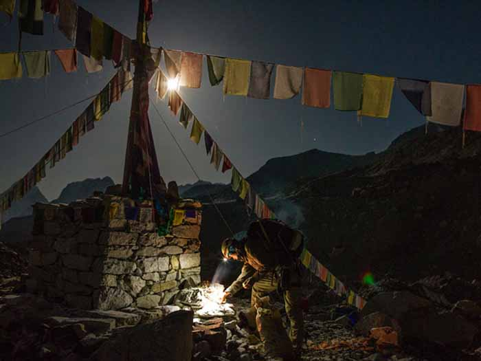 "Before sunrise Danuru Sherpa burns juniper in an offering at Base Camp. A seasoned Everest hand, he first summited at age 18. Now 33, he has reached the peak at least 12 times. Why keep climbing? Danuru, who has two young daughters at school in Kathmandu, told writer Mark Jenkins: ""Because I need the money. Photograph by Andy Bardon"