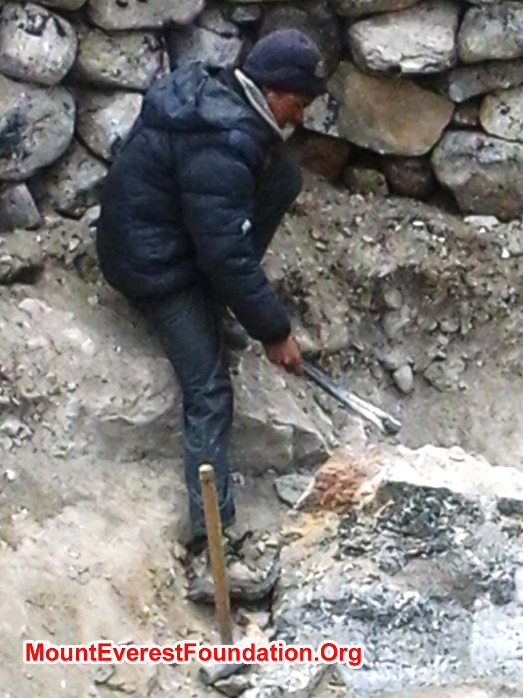 Porter chops stone inside a new human waste pit at Kyapa Yul