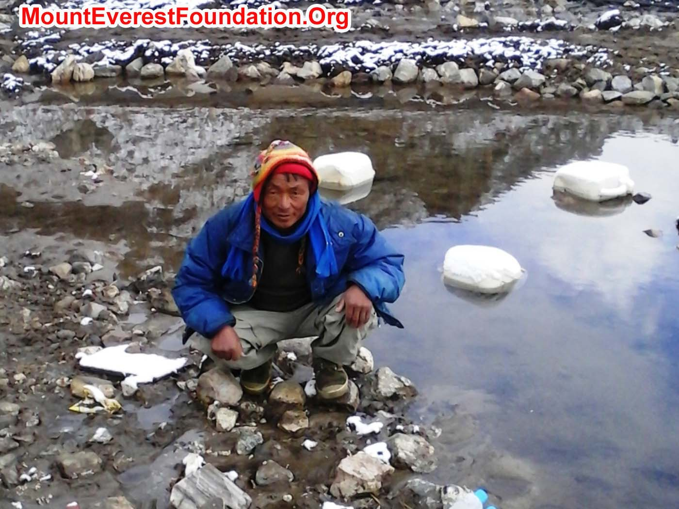 Rukman Sunwar collects a water sample from Gorak Shep Lake. Rubbish floats in the pool behind him