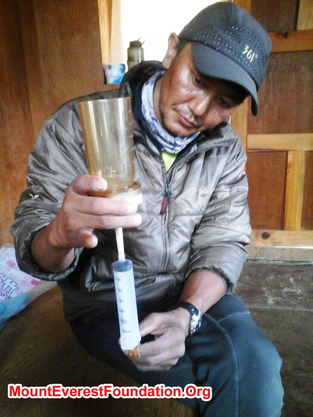 Thile Nuru Sherpa filters a water sample through a petri dish innoculation grid
