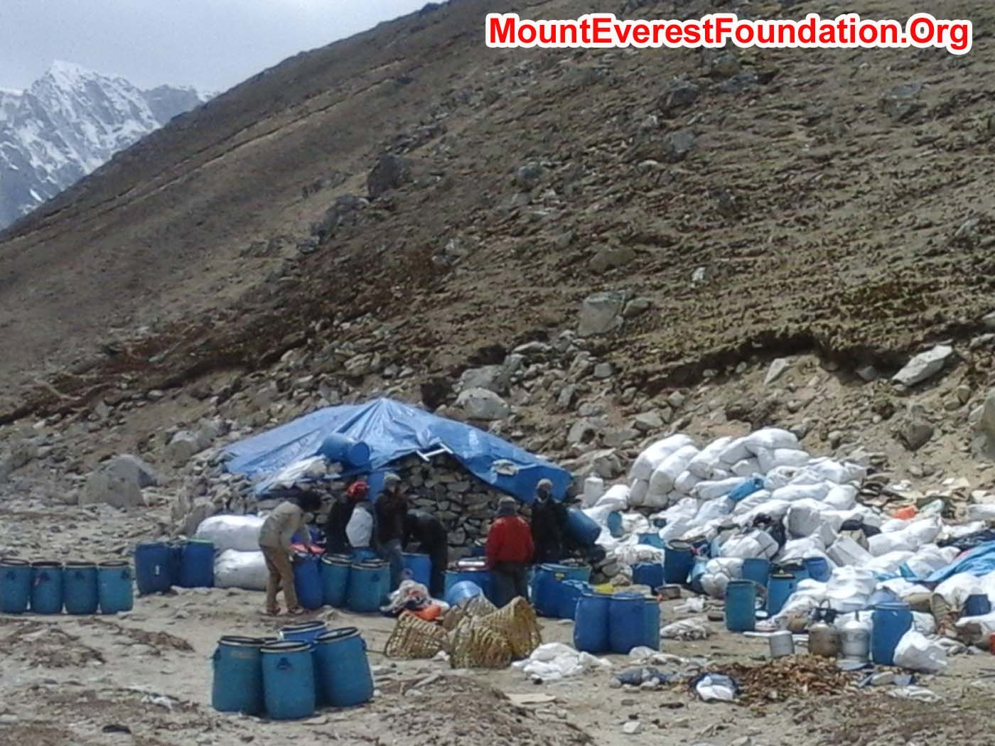 Workers at Gorak Shep sorting out tins, bottles, paper and plastic from Everest basecamp. Kala Pattar and Mount Lobuche in the background