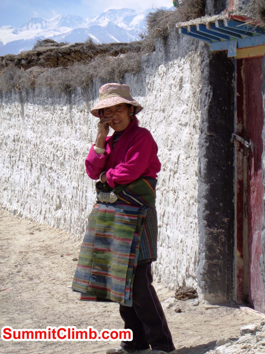 Tibetan plateau woman stands outside her house with Mount Cho Oyu and Everest in the background. Sacha Guittet photo