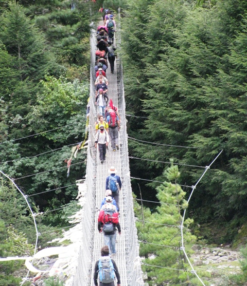 Trekkers on a suspension bridge on the trail to Everest. Photo by Ron and Dee Haberern