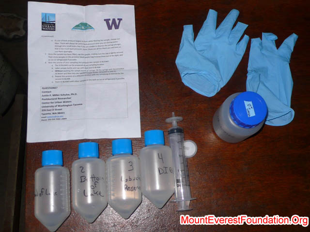 Water sampling instruction sheet, water samples, and equipment on the table at the lodge in Lobuche