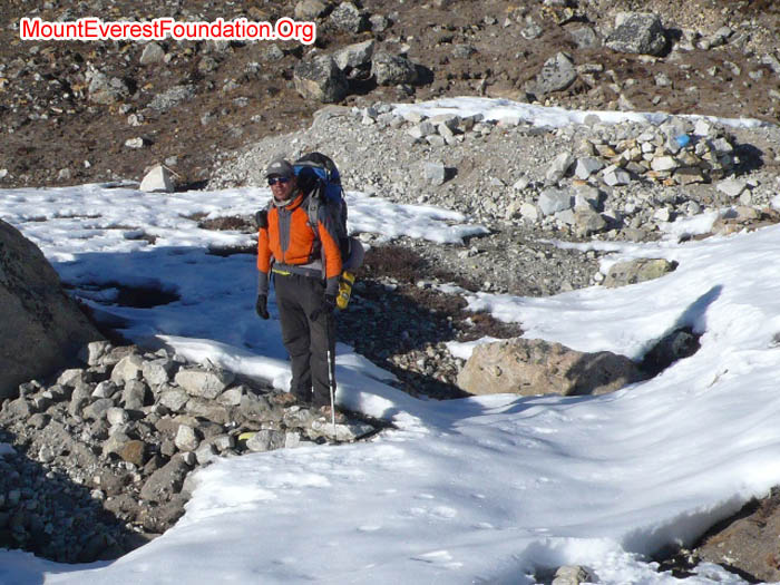Tanji Sherpa standing in the Kyakpa Yul, surrounded by the newest waste deposit from Everest base camp.
