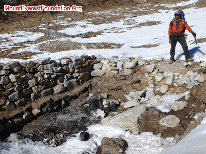 Tenji Sherpa standing in front of pit for burning rubbish in Gorak Shep.
