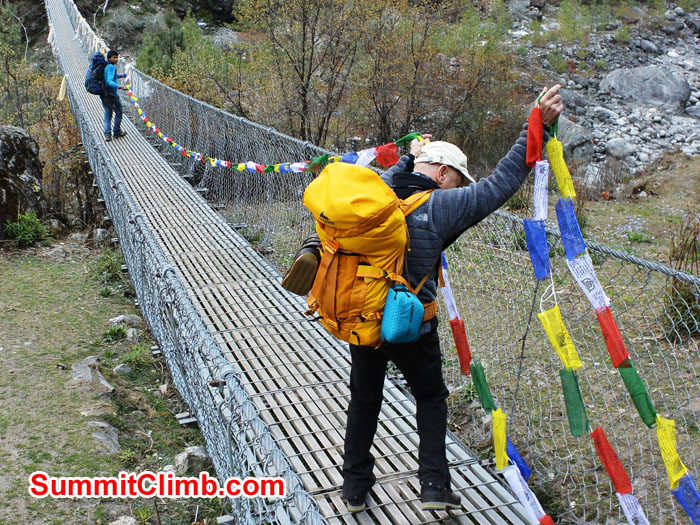 Edward and Laxman Hanging Prayer Flags on the Thada Koshi Bridge. Photo by Mike Fairman
