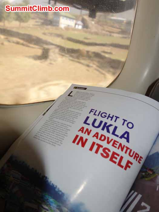 Flight landing at Lukla; onboard magazine open; Lukla village out of the window. Photo David Maidment