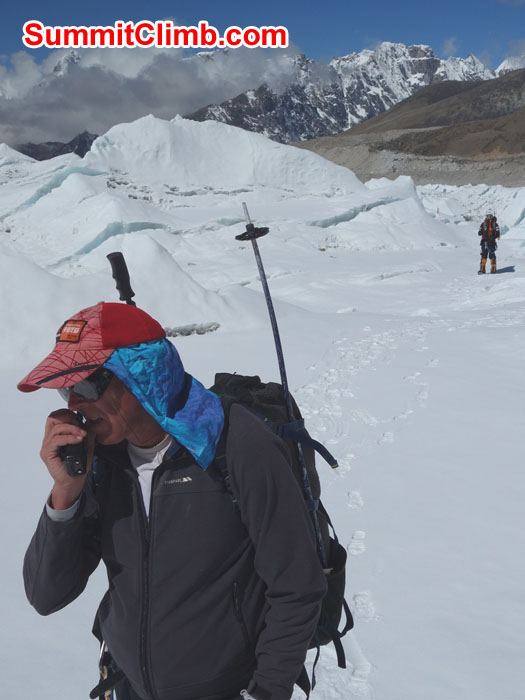 Dan calls basecamp on the radio to tell them the icefall ladders and ropes have been removed. Photo by David Maidment