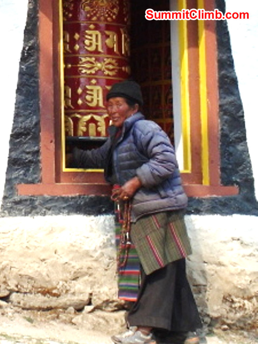 Sherpa Grandmother spins a prayer wheel in Tengboche Monastery. Monika Witkowska Photo.