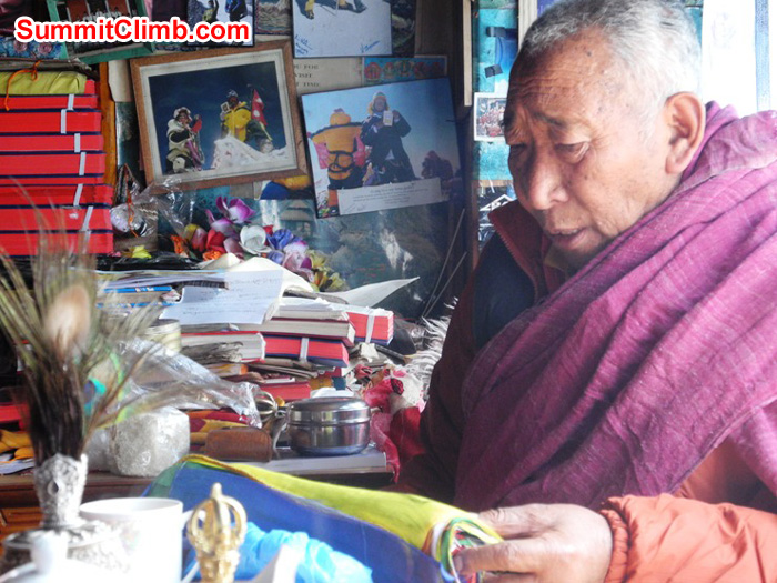 Pangboche's Lama Geshe reading the SummitClimb prayer flags during expedition blessing ceremony. Violetta Pontinen Photo.