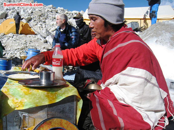 Lama Tashi scoops up a handfull of rice to toss onto the basecamp alter during the blessing ceremony. Scott Smith Photo.