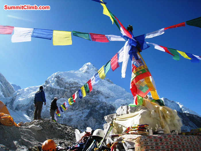 Sherpas putting up prayer flags in basecamp. Summits of Lhotse and Nuptse in background. Scott Smith Photo.