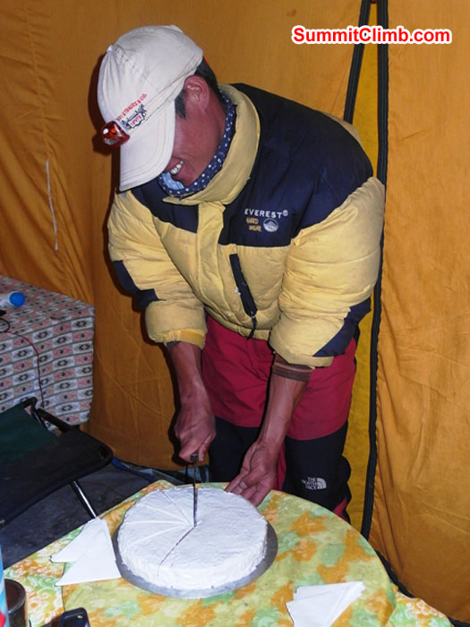 Kamal Bahadur cuts the cake on a celebration night in basecamp. Monika Witkowska Photo.
