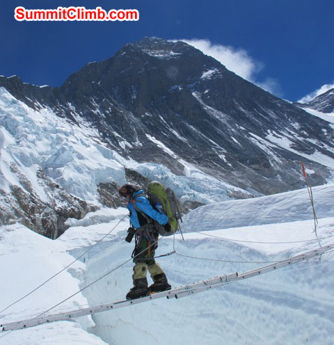 Jangbu Sherpa crosses a long ladder with Mt. Everest fully in the background. Monika Witkowska Photo