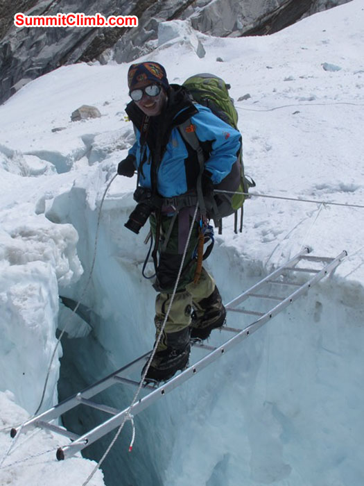 Jangbu Sherpa, 14 time Everest summiter, crosses a ladder in the Khumbu icefall. Monika Witkowska Photo