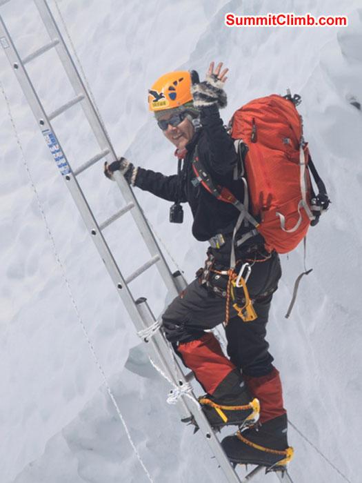 Monika Witkowska climbing a ladder in the icefall. Violetta Pontinen Photo