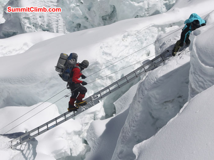 Slavomir Fila climbs a ladder in the Khumbu Icefall while Jangbu Sherpa holds the lines. Monika Witkowska Photo