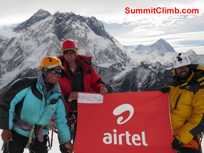 Jangbu, Dan and Elmo holding Nandini Chol Raj's Airtel flag in front of Everest, Nuptse, and Makalu. Photo b David Maidment