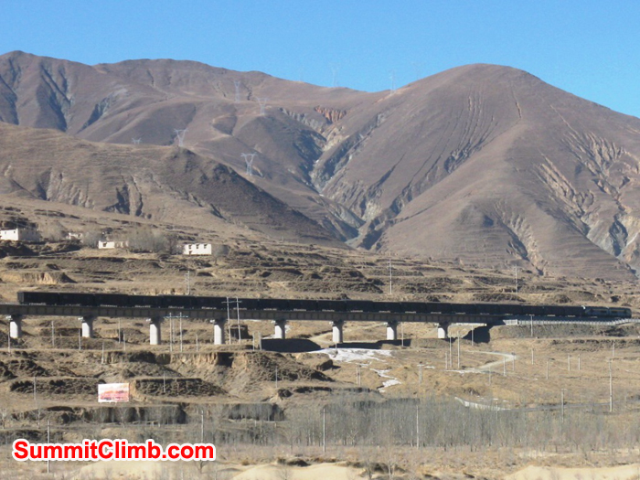 Freight train whisks along  an elevated concrete railway  traversing the plateau from Lhasa to Shigatse.