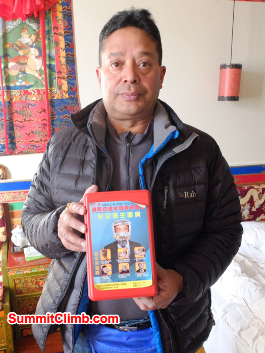 Murari Sharma holding emergency oxygen hood in Shigatse hotel room