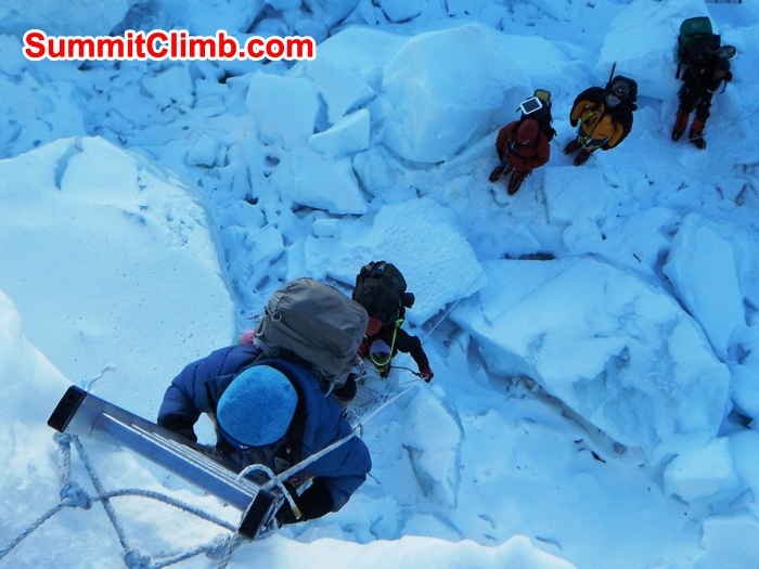 Paula cimbs a five section ladder in the Khumbu icefall while Lhakpa, Cat, James, and Karma wait patiently. Mike Fairman Photo