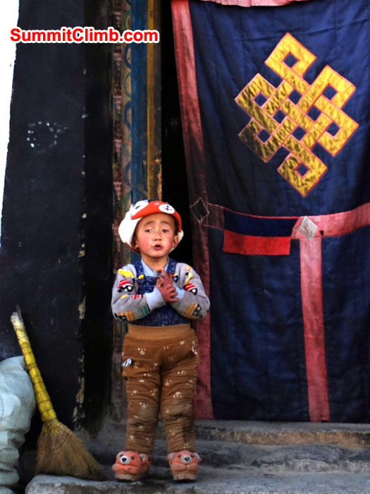 Tingri boy in doorway with broom
