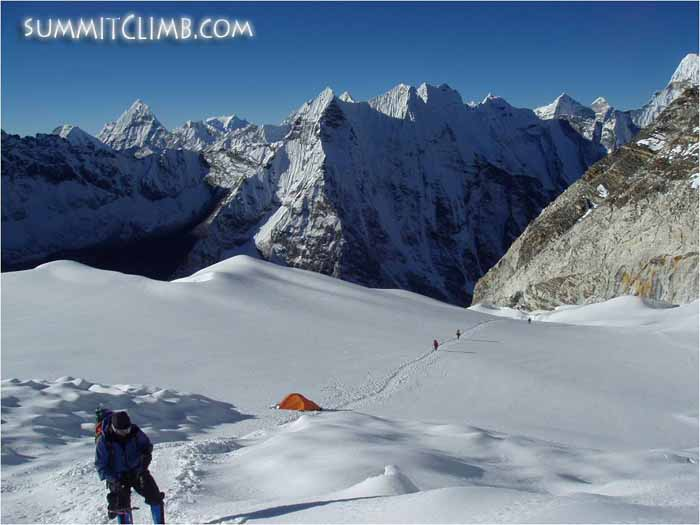 Members crossing the final snow plateau before the summit headwall. In the background is the famous Amphu-Lapsa pass and on the far right the north face of Ama Dablam