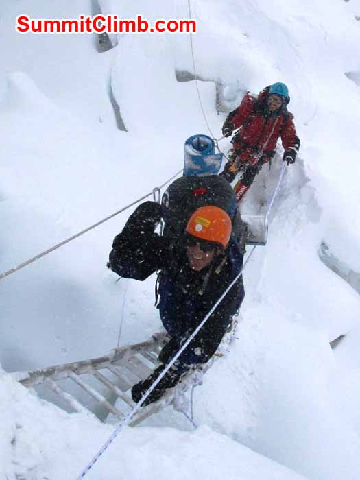 Dan descends a ladder while Vincent Callet belays while descending from Camp 2 to Camp 1 during a snow storm