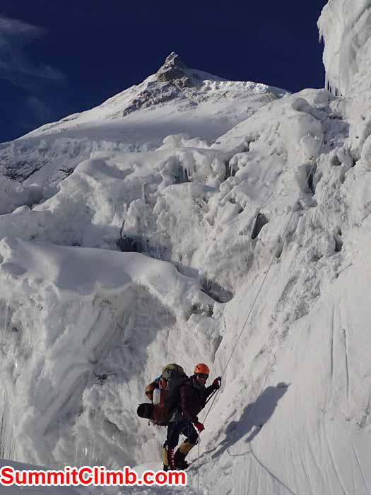 Jangbu Sherpa climbing the icefall in the early morning hours. Manaslu summit in background. Marin Minamiya Photo.