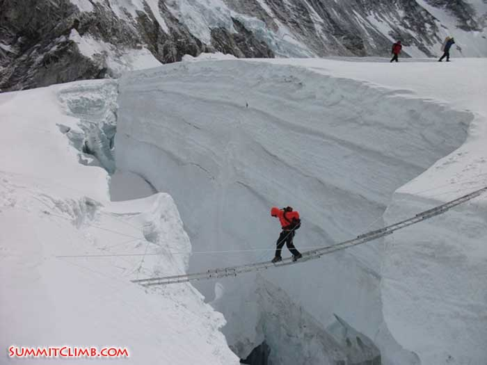 A sherpa crossing five ladders over a crevasse (Alex Holt).
