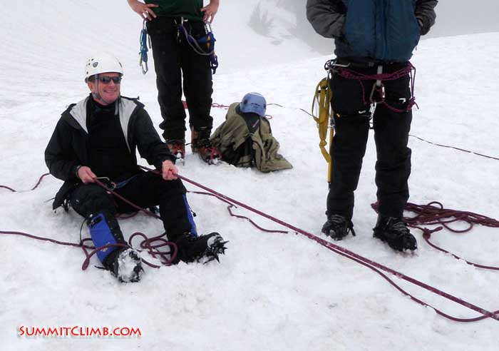 Randy works on his hip-belay technique as he helps a fellow participant climb up the slope (Anna Moll).