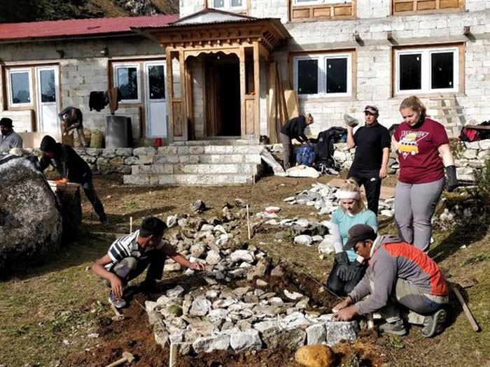 Volunteers help workers lay the new walkway