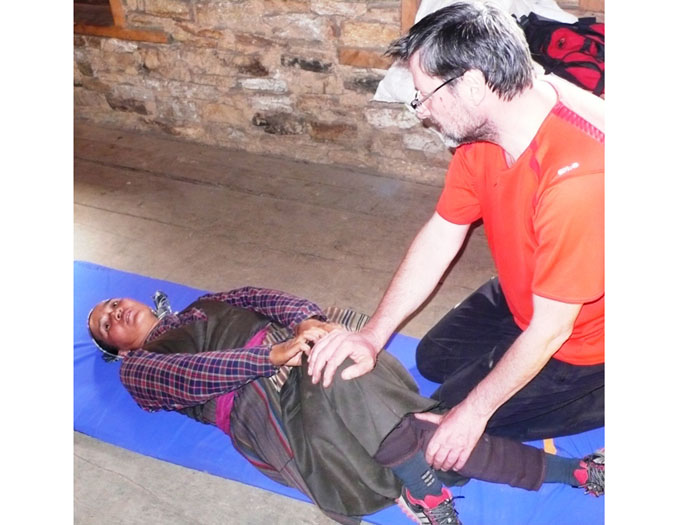 Wolfgang Nicola,  physiotherapist from Germany, shows Puti Sherpa how to stretch her sore back. Villagers work hard and develop physical problems which can be helped sustainably by stretching and massage.
