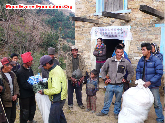 everyone watches while Gyel Chiri Sherpa hands out a blanket to one of the poorest people in the village, a deaf, mute, and mentally challenged person.