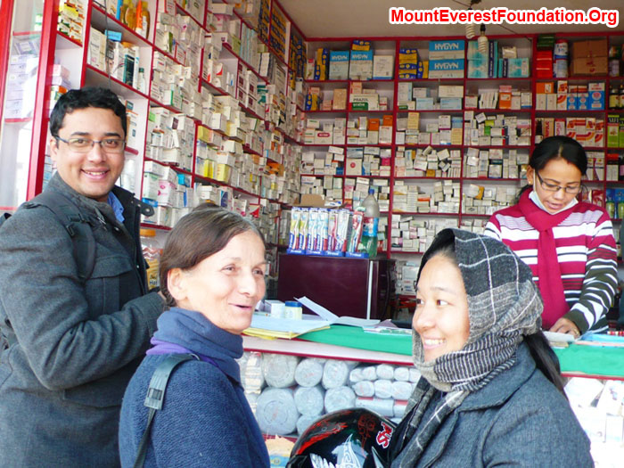 Deha Shrestha from the Mount Everest Foundation with Marie Serys and Yanke Sherpa, filling the prescription for Nimke Sherpa at the chemist's shop.