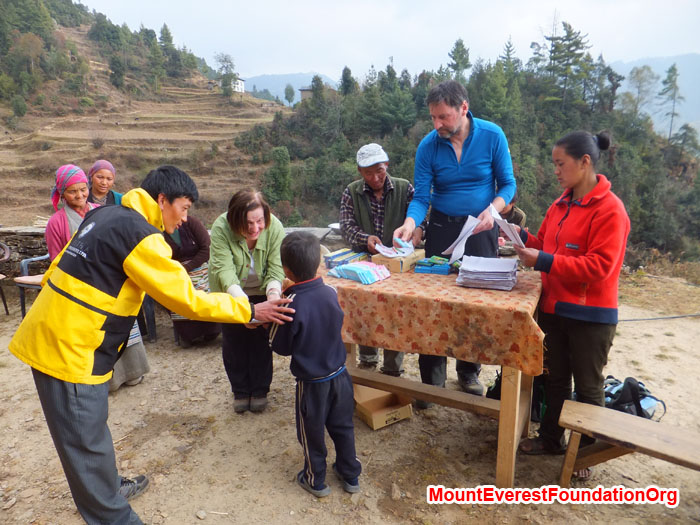 Teacher Jamyang, Anne Kates, Jangbu Sherpa, Wolfgang Nicola and Yangjie Sherpa distribute books, paper, and pens to a local student in Dhorkharka village. Photo by Dan Mazur